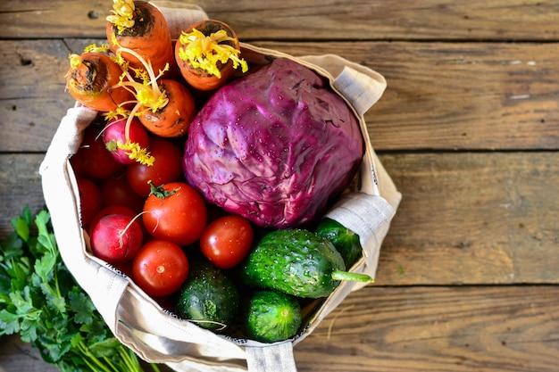 Ravanelli, pomodori, cetrioli, carote, cavolo rosso in un sacchetto. vista dall'alto. borsa in tessuto di lino.