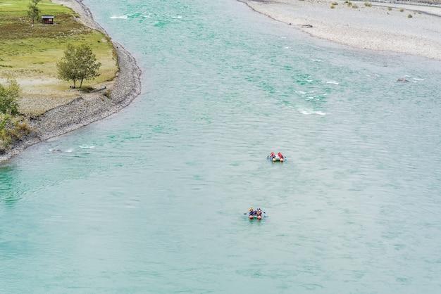 Rafters che fanno rafting lungo un fiume di montagna fiume katun nei monti altai in autunno