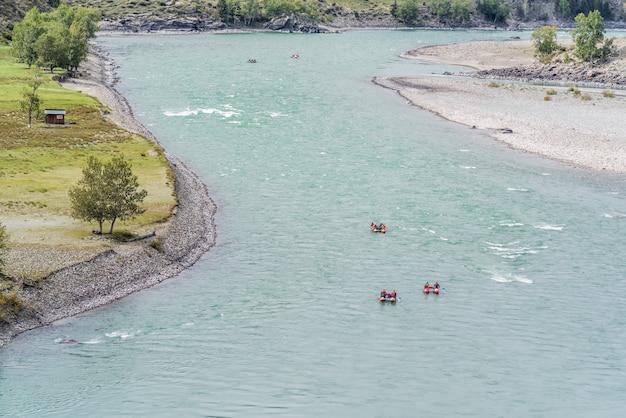 Rafters che fanno rafting lungo un fiume di montagna. la foto è stata scattata sul fiume katun nei monti altai, in autunno