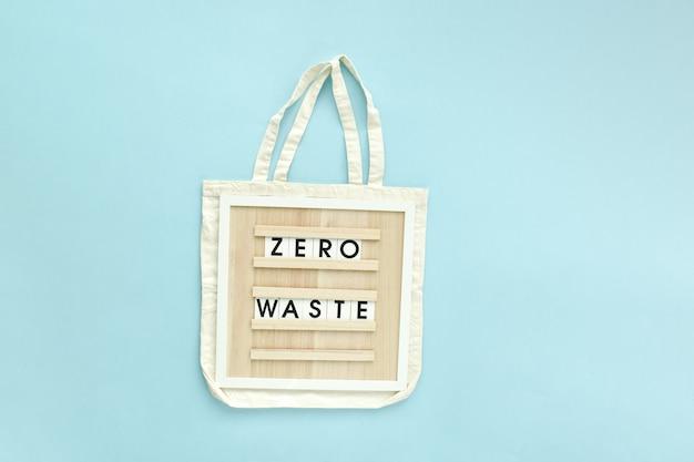 Un sacchetto di stracci con il messaggio di testo zero rifiuti su sfondo azzurro. poster, banner è un prodotto ecologico. uno spazio vuoto. layout piatto, vista dall'alto, un posto da copiare.