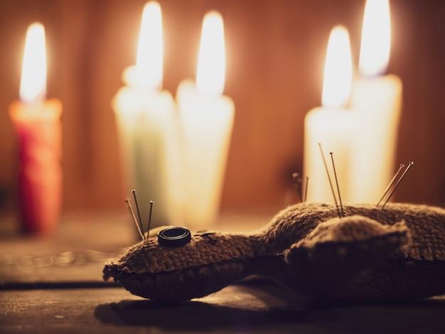 Bambola di pezza voodoo trafitto con aghi, sdraiato su un tavolo di legno circondato da candele accese, primo piano.