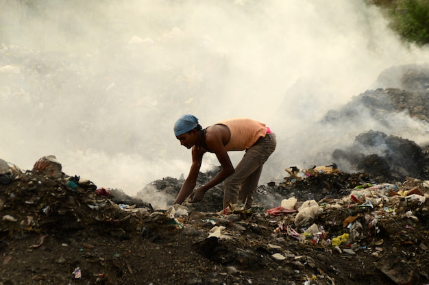 I raccoglitori di stracci cercano materiale riciclabile nella spazzatura terra e inquinamento atmosferico in india