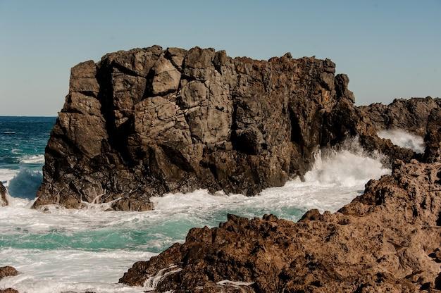 Mare impetuoso che batte le rocce con onde bianche con schiuma sotto il cielo limpido