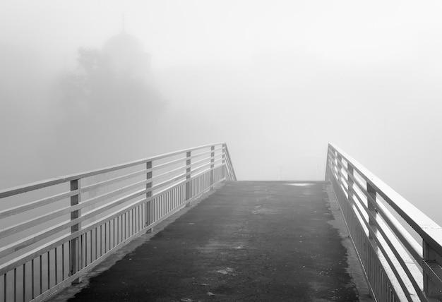 La ringhiera della stazione ferroviaria colma la sagoma della cattedrale nella nebbia mattutina