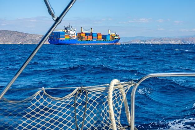 Ringhiera di uno yacht a vela in sfocatura. nave portacontainer con molto carico a bordo. tempo soleggiato