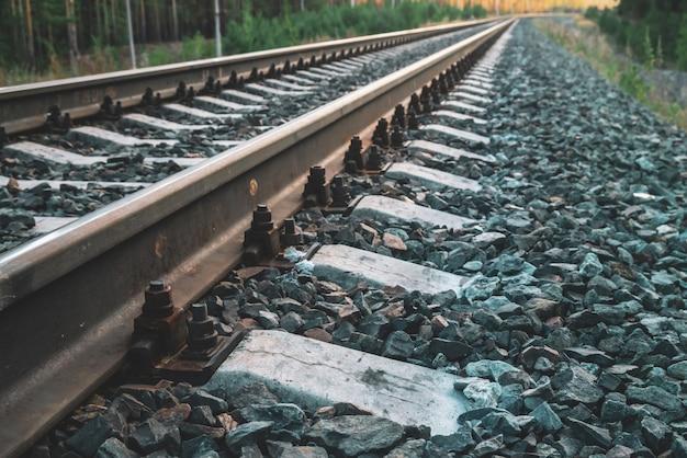 Ferrovia al crepuscolo con spazio di copia. rotaie, traversine, chiusure e pietra frantumata da vicino. viaggiare in treno. viaggio su binario alla luce del sole. modello nei toni del blu scuro.