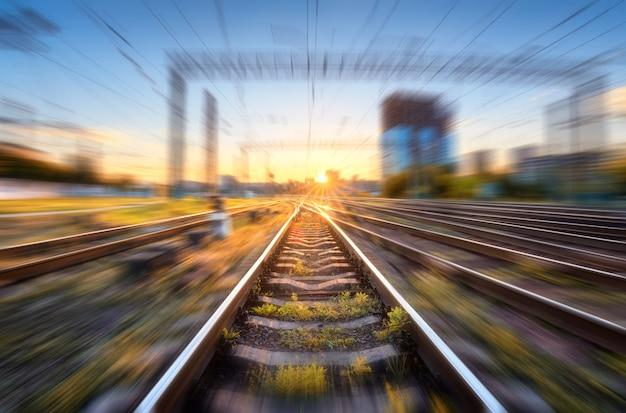 Ferrovia con effetto motion blur al tramonto. paesaggio concettuale industriale con stazione ferroviaria sfocata, edifici, erba verde, cielo blu e luce solare arancione la sera. linea ferroviaria. sfondo