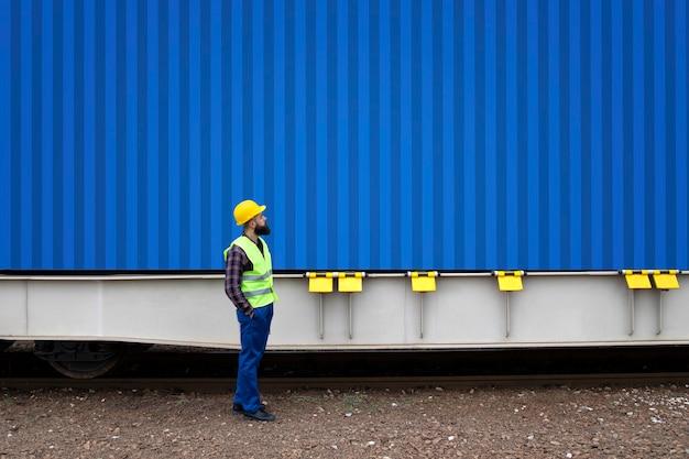 Operaio della ferrovia che esamina il contenitore del carico.