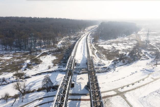 Ponte ferroviario sul fiume in una giornata invernale con binari che vanno nella foresta. vista aerea del drone.