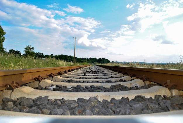 Le rotaie ferroviarie e le traversine hanno sparato in basso sopra il primo piano del suolo su uno sfondo di cielo nuvoloso