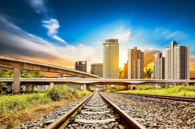 La ferrovia e la strada sono legate alla città sul cielo blu sullo sfondo dell'ora del tramonto