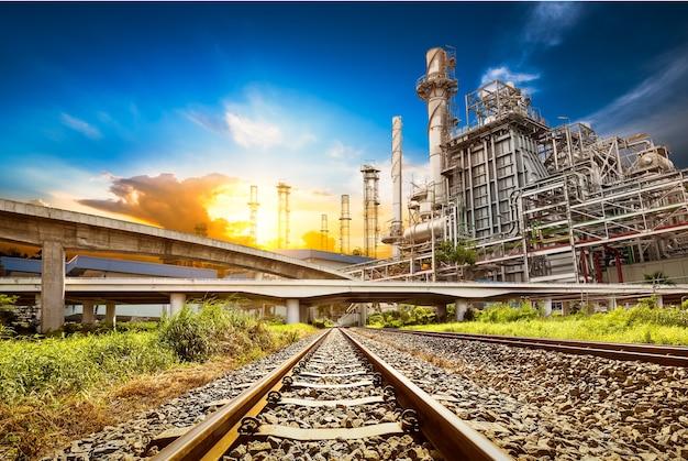 La ferrovia e la strada sono legate all'edificio della centrale elettrica sullo sfondo del tramonto