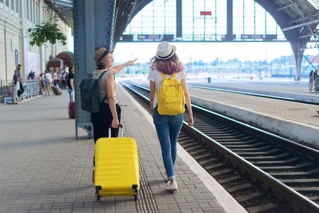 Stazione ferroviaria, persone passeggeri con bagagli