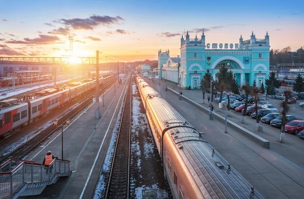 Stazione ferroviaria e treni sui binari a smolensk sotto il cielo blu di primavera al tramonto