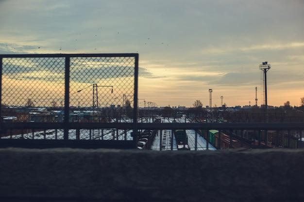 Stazione ferroviaria con treni merci e container al tramonto. priorità bassa industriale urbana.