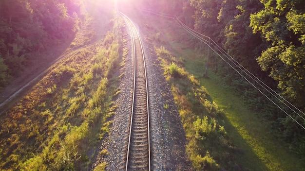Ferrovia all'alba attraverso paesaggi naturali verdi, il bagliore della luce solare nell'obiettivo della fotocamera