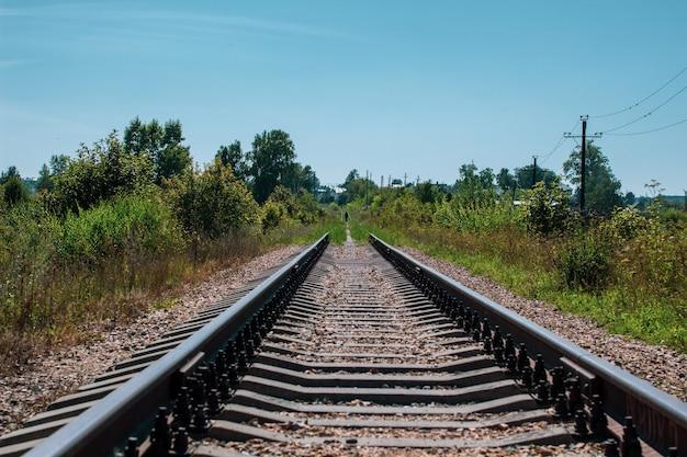 Binari ferroviari e ghiaia che portano alla distanza infinita.