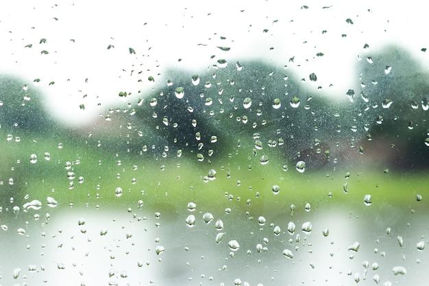 Goccia di pioggia sul fondo della finestra di vetro.