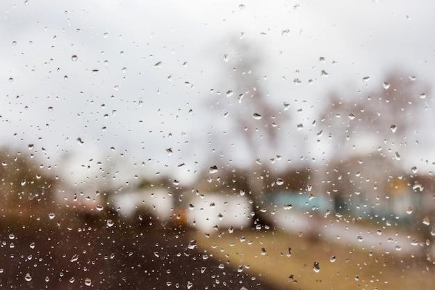 Gocce di pioggia sul vetro trasparente, case e alberi sfocati lontani