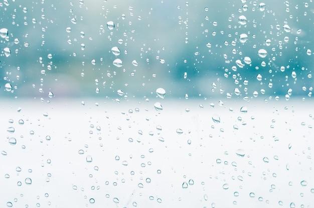 Gocce di pioggia e acqua congelata su sfondo di vetro del finestrino, tonalità blu