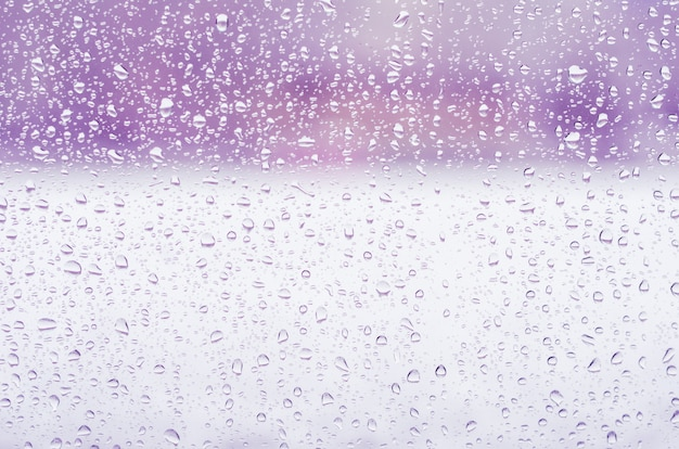 Gocce di pioggia e acqua congelata sul fondo del vetro di finestra, tonalità porpora