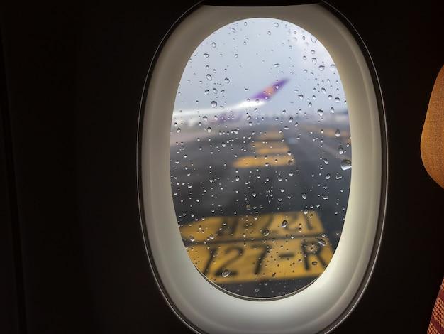 La pioggia cade sul vetro fuori dal finestrino dell'aereo passeggeri che è parcheggiato sulla pista.