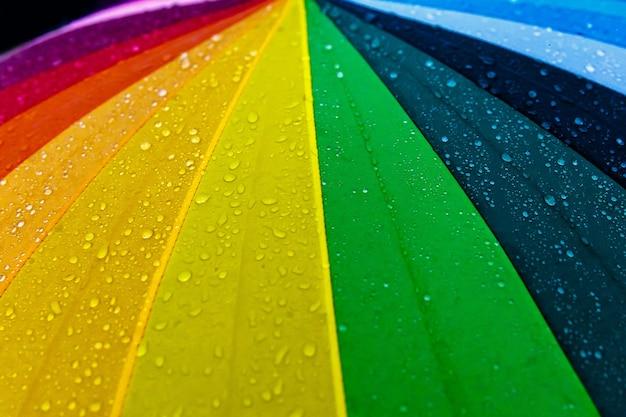 Gocce di pioggia sull'ombrello multicolore arcobaleno