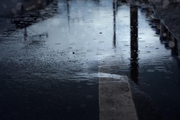 Gocce di pioggia che schizzano durante la caduta della pioggia dura di notte, messa a fuoco selettiva. sfondo stagione piovosa.