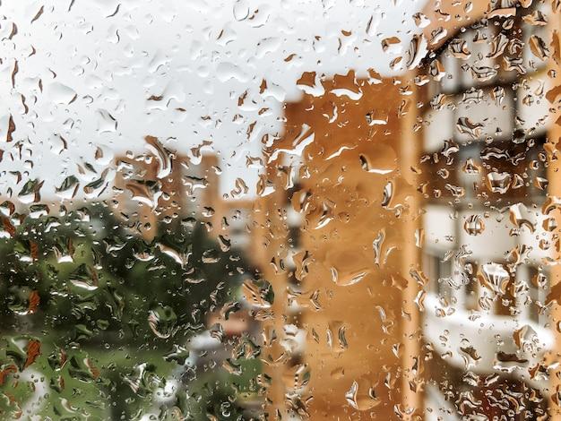 Gocce di pioggia sul vetro della finestra in un giorno di pioggia