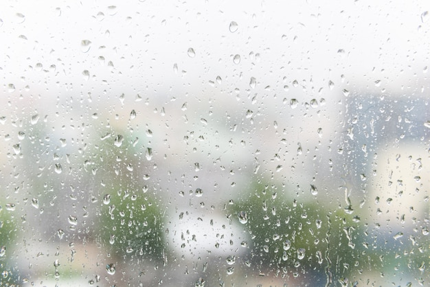 Gocce di pioggia sul vetro della finestra con sfondo sfocato scuro.
