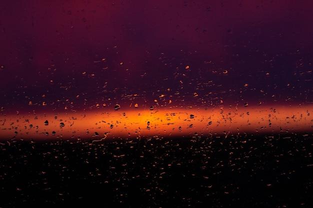 Gocce di pioggia sulla finestra sul sunsret (superficie rosa blu scuro)