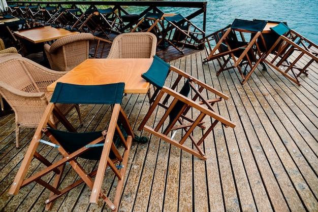 La pioggia bagna i tavoli e le sedie di un ristorante senza clienti in un lago italiano per turisti.
