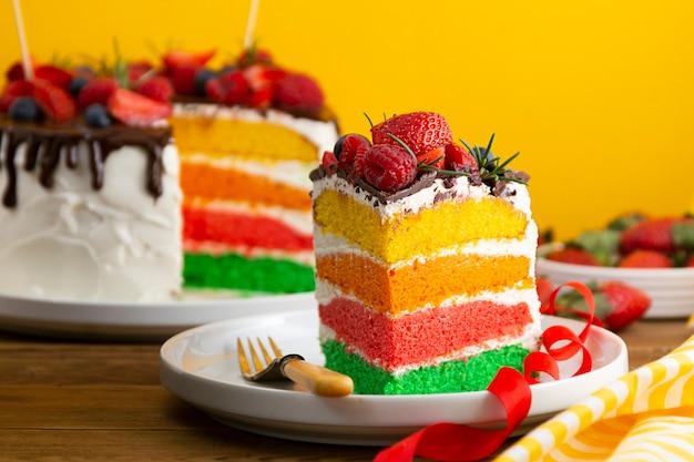 Torta di compleanno arcobaleno con frutti di bosco freschi su sfondo giallo