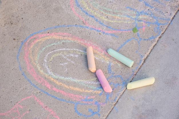Gesso arcobaleno disegnato sull'asfalto, simbolo della comunità lgbt, pastelli sul disegno del bambino a terra