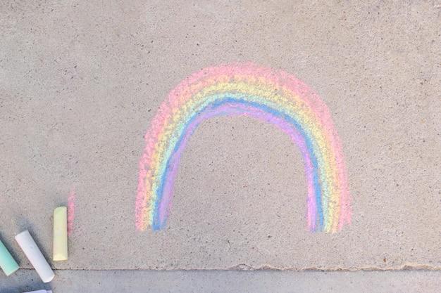 Gesso arcobaleno disegnato sull'asfalto, simbolo della comunità lgbt, pastelli a terra vista dall'alto
