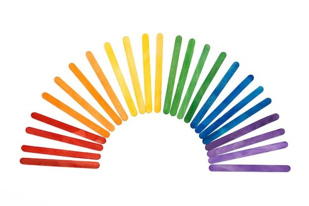 Bastoncini di gelato in legno color arcobaleno su concetto lgbt bianco