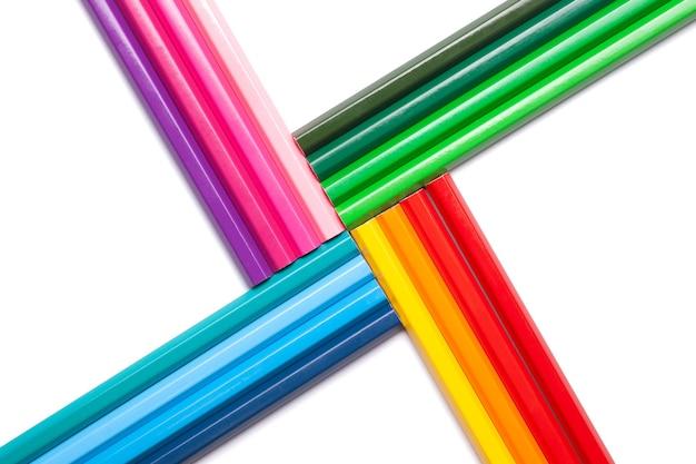 Matite colorate non ombreggiate arcobaleno a forma di croce greca, isolate su uno sfondo bianco.