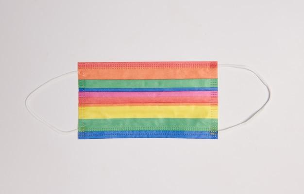 Maschera facciale colorata arcobaleno, protezione da virus, simbolo di sicurezza nel mese del gay pride da coronavirus, superficie blu. distanza sociale, covid-19, concetto dei diritti lgbt. copia spazio, testo, disposizione piatta, vista dall'alto
