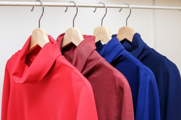 Colori dell'arcobaleno scelta di vestiti casual su ganci di legno in un negozio