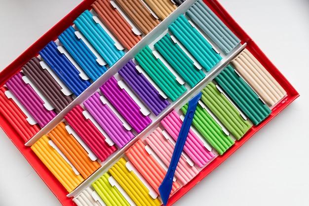 Casella di plastilina di colori dell'arcobaleno isolata su bianco