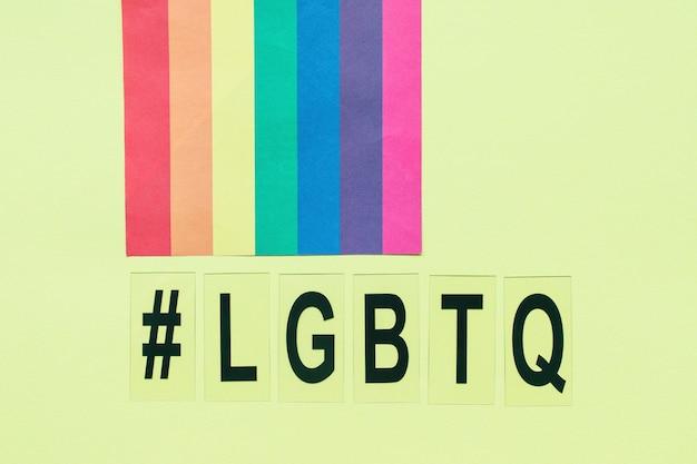 Bandiera arcobaleno, simbolo hashtag e lettere lgbtq su giallo