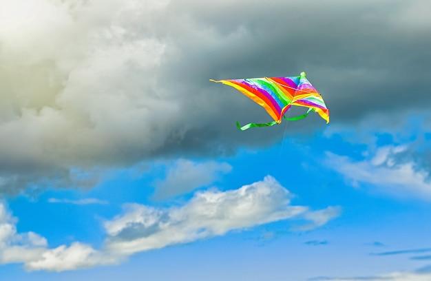 Aquilone arcobaleno che vola nel cielo blu con nuvole in estate con copyspace