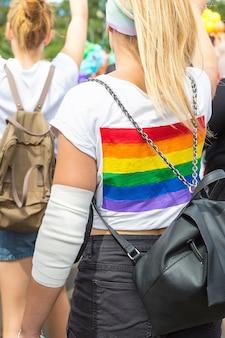 Bandiera arcobaleno lgbt sullo zaino della signora in mezzo alla folla di persone su prague pride parade