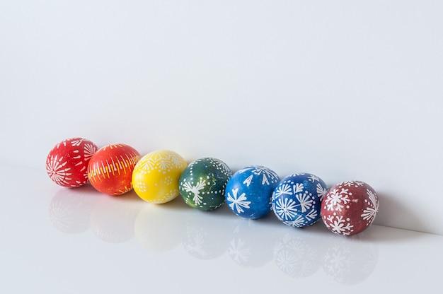 Linea dell'arcobaleno di uova di pasqua su fondo bianco con la riflessione. concetto di vacanza di pasqua.