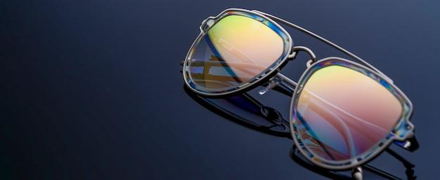 Occhiali da sole con mirroring arcobaleno sul tavolo scuro, copia dello spazio