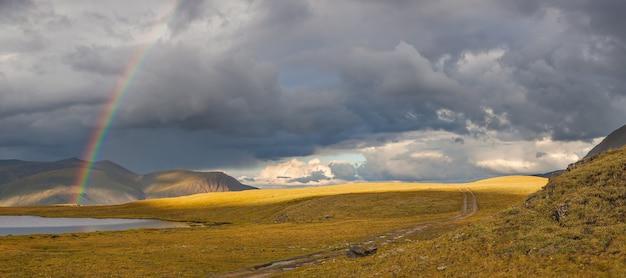 Arcobaleno in una valle di montagna, luci contrastanti