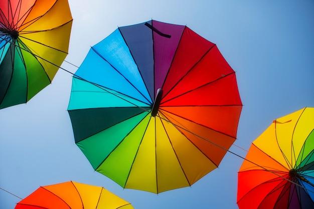 Ombrelli multicolori arcobaleno dalla pioggia sullo sfondo del cielo.
