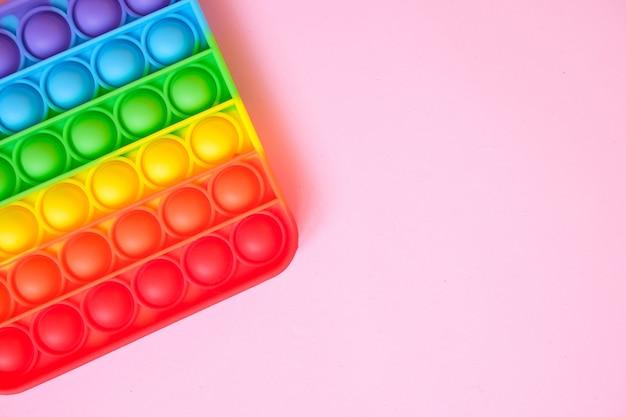 Arcobaleno pop it giocattolo agitarsi su uno sfondo di spazio vuoto della copia. sfondo rosa