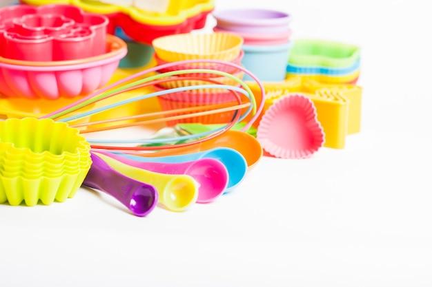 Utensili da pasticceria in silicone arcobaleno su sfondo bianco