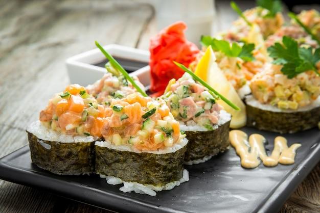 Rainbow sushi roll con salmone, anguilla, tonno, avocado, gambero reale, crema di formaggio philadelphia, tobica caviale, chuka. menu di sushi. cibo giapponese.